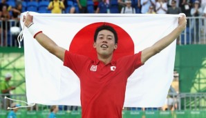 RIO DE JANEIRO, BRAZIL - AUGUST 14: (EDITORS NOTE: Retransmission with alternate crop.) Kei Nishikori of Japan celebrates with the Japanese flag after winning the singles bronze medal match against Rafael Nadal of Spain on Day 9 of the Rio 2016 Olym...