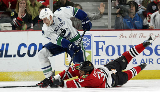 """Sliding Tackle"" mal anders: Dustin Byfuglien (r.) von den Chicago Blackhawks kämpft im NHL-Match gegen die Vancouver Canucks mit Sami Salo verzweifelt um den Puck"