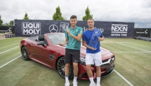 STUTTGART, GERMANY - JUNE 13: Dominic Thiem of Austria (L) and Philipp Kohlschreiber of Germany pose with their trophies in front of the prize car after the final match on day 10 of Mercedes Cup 2016 on June 13, 2016 in Stuttgart, Germany. (Photo b...